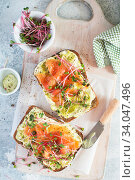 Healthy eating concept. Toast with avocado cream and smoked salmon on the white wooden board. Smoked salmon, cream cheese and pesto toast sandwiches with radish microgreens sprouts. Стоковое фото, фотограф Nataliia Zhekova / Фотобанк Лори