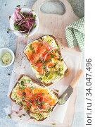Купить «Healthy eating concept. Toast with avocado cream and smoked salmon on the white wooden board. Smoked salmon, cream cheese and pesto toast sandwiches with radish microgreens sprouts.», фото № 34047496, снято 20 января 2020 г. (c) Nataliia Zhekova / Фотобанк Лори
