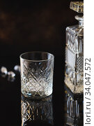 Empty Glass for whiskey or bourbon with and a crystal square decanter on the black reflective surface. Стоковое фото, фотограф Nataliia Zhekova / Фотобанк Лори