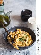 Купить «Chickpeas hummus in the black bowl decorated with sesame seeds and chickpeas greens. Vegan recipes, plant-based dishes. Green living concept. Organic food. Vegetarian», фото № 34047584, снято 2 марта 2020 г. (c) Nataliia Zhekova / Фотобанк Лори