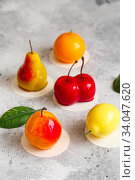 Mousse dessert in the shape of a pear fruit, orange fruit, apricot, lemon and cherry. Mousse cake. Стоковое фото, фотограф Nataliia Zhekova / Фотобанк Лори