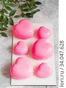 Купить «Pink Mousse dessert in the shape of hearts. Mousse cake for Valentine Day», фото № 34047628, снято 1 февраля 2020 г. (c) Nataliia Zhekova / Фотобанк Лори