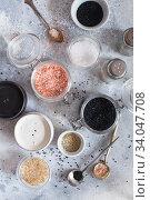 Купить «Mix of different salt types on grey concrete background. Sea salts, black and pink Himalayan salt crystals, powder. collection of different types of salt. Top view flat lay. Different Sea salts», фото № 34047708, снято 11 февраля 2020 г. (c) Nataliia Zhekova / Фотобанк Лори