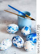 Купить «Dyed Easter eggs. Сlassic blue Easter eggs on the grey background. Blue speckled easter eggs with paint and brushes. Decorating eggs, preparing for Easter», фото № 34047720, снято 27 февраля 2020 г. (c) Nataliia Zhekova / Фотобанк Лори