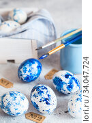 Купить «Dyed Easter eggs. Сlassic blue Easter eggs on the grey background. Blue speckled easter eggs with paint and brushes. Decorating eggs, preparing for Easter», фото № 34047724, снято 27 февраля 2020 г. (c) Nataliia Zhekova / Фотобанк Лори
