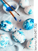Купить «Dyed Easter eggs. Сlassic blue Easter eggs on the grey background. Blue speckled easter eggs with paint and brushes. Decorating eggs, preparing for Easter», фото № 34047732, снято 27 февраля 2020 г. (c) Nataliia Zhekova / Фотобанк Лори