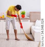 Купить «Young handsome man cleaning in the bedroom», фото № 34048024, снято 28 июня 2018 г. (c) Elnur / Фотобанк Лори