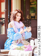 Купить «Outdoor portrait of beautiful woman at the table in a street city cafe. Urban romantic portrait of beautiful girl wearing light blue dress», фото № 34048156, снято 24 сентября 2019 г. (c) Nataliia Zhekova / Фотобанк Лори