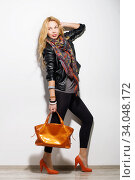 Купить «ashion model girl full-length portrait dressed in black leather jacket, leggings, colorful scarf and modern accessories holding orange bag.», фото № 34048172, снято 13 марта 2016 г. (c) Nataliia Zhekova / Фотобанк Лори