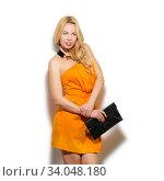 Fashion model girl portrait in orange dress and modern accessories holding clutch bag. Стоковое фото, фотограф Nataliia Zhekova / Фотобанк Лори