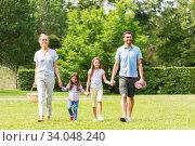 Купить «family with picnic basket walking in summer park», фото № 34048240, снято 30 июня 2019 г. (c) Syda Productions / Фотобанк Лори