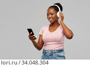Купить «african woman in headphones listening to music», фото № 34048304, снято 26 января 2020 г. (c) Syda Productions / Фотобанк Лори