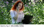 Young red-haired woman work on laptop computer and talking on a mobile phone among flowers in a city park. Стоковое видео, видеограф Алексей Кузнецов / Фотобанк Лори