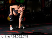 Pregnant female athlete doing single sumo deadlift high pull with dumbbell. Стоковое фото, фотограф Zoonar.com/Serghei Starus / easy Fotostock / Фотобанк Лори