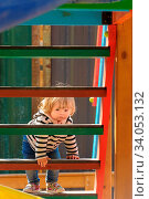 Cute little blond toddler girl climbing stairs of a children's slide at playground. Стоковое фото, фотограф Zoonar.com/Serghei Starus / easy Fotostock / Фотобанк Лори