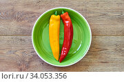 Yellow and red pods of pepper on a green plate on a wooden tabletop. Стоковое фото, фотограф Евгений Харитонов / Фотобанк Лори