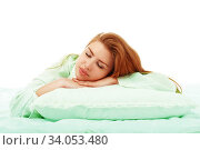 Young beautiful girl sleeps in the bed hugging a pillow on his stomach. Healthy sleep. Стоковое фото, фотограф Nataliia Zhekova / Фотобанк Лори