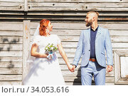 Купить «Just married loving hipster couple in wedding dress and suit in the park. Happy bride and groom walking running and dancing. Romantic Married young family.», фото № 34053616, снято 5 октября 2018 г. (c) Nataliia Zhekova / Фотобанк Лори
