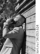 Купить «view of a hipster young man looking away from the camera while smoking a cigarette.», фото № 34053624, снято 5 октября 2018 г. (c) Nataliia Zhekova / Фотобанк Лори