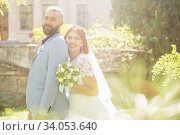 Купить «Just married loving hipster couple in wedding dress and suit in the park. Happy bride and groom walking running and dancing. Romantic Married young family.», фото № 34053640, снято 5 октября 2018 г. (c) Nataliia Zhekova / Фотобанк Лори