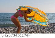 Smiling woman in sunglasses and bikini at the seaside girl trying to set an umbrella. Стоковое фото, фотограф Константин Сиятский / Фотобанк Лори