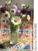 Bouquet of beautiful multicolored wildflowers in a glass vase on a decorative background. Стоковое фото, фотограф Яна Королёва / Фотобанк Лори