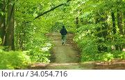 Young man in hoodie jogging in the green forest. Стоковое видео, видеограф Константин Шишкин / Фотобанк Лори