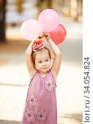 Купить «Portrait of laughing and playing little girl holding colorful balloons.», фото № 34054824, снято 27 сентября 2015 г. (c) Nataliia Zhekova / Фотобанк Лори