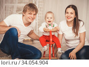 Lovely Baby boy in Santa Claus costume for Christmas. Mother, father and little son playing. Happy family. Стоковое фото, фотограф Nataliia Zhekova / Фотобанк Лори