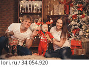 Lovely Baby boy in Santa Claus costume for Christmas. Mother, father and little son playing. Стоковое фото, фотограф Nataliia Zhekova / Фотобанк Лори