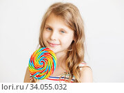 lovely little girl with big delicious lollipop against a white background. Стоковое фото, фотограф Nataliia Zhekova / Фотобанк Лори
