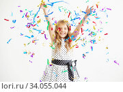 Portrait of a child throws up multi-colored tinsel and confetti. Стоковое фото, фотограф Nataliia Zhekova / Фотобанк Лори