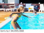 Купить «Happy kid playing in blue water of swimming pool. Little girl learning to swim. Summer vacations concept. Cute girl swimming in pool water. Child splashing and having fun in pool», фото № 34055068, снято 10 августа 2016 г. (c) Nataliia Zhekova / Фотобанк Лори