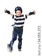 Купить «Little boy in protection helmet and in the knee and arm ruffles riding his scooter», фото № 34055372, снято 18 марта 2015 г. (c) Nataliia Zhekova / Фотобанк Лори