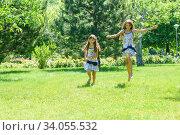 Две девочки весело бегут по зеленому газону в парке. Стоковое фото, фотограф Иванов Алексей / Фотобанк Лори