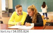 Купить «Emotional university students sitting at desk and reading homework together in classroom», видеоролик № 34055824, снято 9 марта 2020 г. (c) Яков Филимонов / Фотобанк Лори