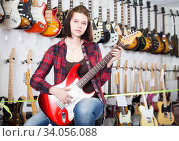 Купить «Female teenager examining various electric guitars», фото № 34056088, снято 14 февраля 2017 г. (c) Яков Филимонов / Фотобанк Лори