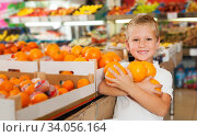 kid holding oranges at fruit section of store. Стоковое фото, фотограф Яков Филимонов / Фотобанк Лори