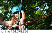 Купить «Extreme rope adventure in the park - smiling woman carefully walks upwards on the suspension rope bridge holding by the ropes above her head», видеоролик № 34078856, снято 7 июля 2020 г. (c) Константин Шишкин / Фотобанк Лори