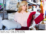 Positive mature woman choosing cotton bedcover in the textile shop. Стоковое фото, фотограф Яков Филимонов / Фотобанк Лори