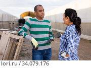 Latino workers talking near wooden pallets outdoors. Стоковое фото, фотограф Яков Филимонов / Фотобанк Лори
