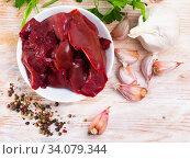 Купить «Image of raw rabbit liver with garlic and greens», фото № 34079344, снято 2 июля 2020 г. (c) Яков Филимонов / Фотобанк Лори