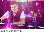Portrait of excited guy with laser pistol playing laser tag in a. Стоковое фото, фотограф Яков Филимонов / Фотобанк Лори