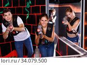 First person view of young people aiming from laser gun in dark laser tag game room. Стоковое фото, фотограф Яков Филимонов / Фотобанк Лори