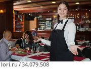 Young waitress meeting guests. Стоковое фото, фотограф Яков Филимонов / Фотобанк Лори