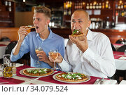 Male friends watching sport match and enjoying pizza in restaurant. Стоковое фото, фотограф Яков Филимонов / Фотобанк Лори