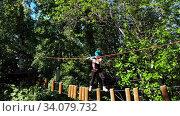 Купить «Extreme rope adventure in the park - woman carefully walks on the rope with stumps attached to it», видеоролик № 34079732, снято 7 июля 2020 г. (c) Константин Шишкин / Фотобанк Лори