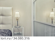 Warm cozy lamp near bed and headboard. Стоковое фото, фотограф Ольга Сапегина / Фотобанк Лори