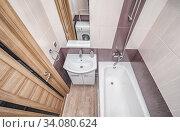 Small beige tile bathroom with bath tube and sink. Стоковое фото, фотограф Ольга Сапегина / Фотобанк Лори