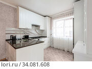 Modern white kitchen interior with beige walls, clean design. Стоковое фото, фотограф Zoonar.com/Serghei Starus / easy Fotostock / Фотобанк Лори